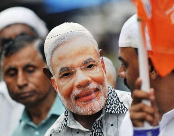 Man with a Modi-mask and a Muslim hat